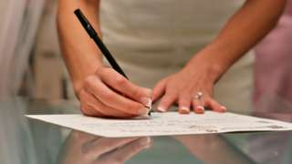 Mãos de noiva assinando papel em cima da mesa