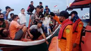 Local fishermen and rescuers hold suspected remains of the Sriwijaya Air plane flight SJ182, which crashed into the sea near Jakarta