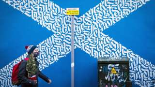 Man in mask walking past a saltire sign