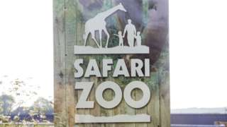 A sign with the zoo name and logo