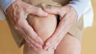 Persona mayor tocando con las manos su rodilla en gesto de dolor