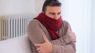 man shivering inside with scarf on