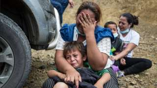 A migrant cries along with her child after police dispersed the caravan of thousands of people that blocked the road in Vado Hondo, Chiquimula, Guatemala, 18 January 2021