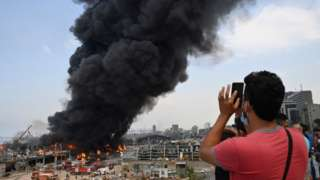 People take pictures as thick smoke billows from a fire at the Port of Beirut, Lebanon, 10 September 2020.