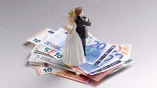 A model of a bride and groom standing on a pile of euros