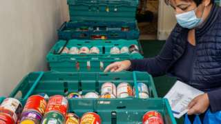 A volunteer packs and prepares food parcels at the Tottenham food bank at Tottenham Town Hall on 21 January 2021 in London, England.
