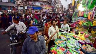 People crowd at a roadside shop to buy water pistols used in the upcoming Holi celebrations, which is a popular Hindu spring festival of colours in Allahabad on March 27, 2021.