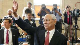 Former US Secretary of State Colin Powell waves before arrival of President Barack Obama at Benjamin Banneker Academic High School in Washington DC on October 17, 2016.