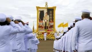 """Thai officials pay respect next to a picture of Thailand""""s King Maha Vajiralongkorn outside the Grand Palace in Bangkok"""