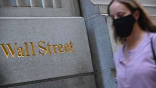 woman in mask walks by Wall Street sign