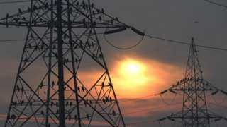 Electricity pylons at sunrise in Delhi, India.