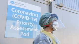 A nurse in protective equipment standing at a Covid-19 testing centre