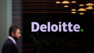 An anonymous man wearing a suit walks past the Deloitte offices in London, UK.