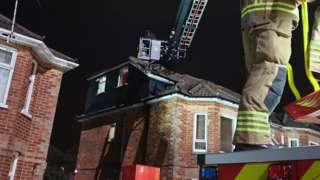 Firefighter operating turntable ladder to reach robbery suspect on roof