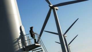 man in front of wind turbine