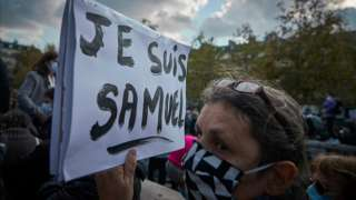 A protester wearing a face mask holds a sign in French that reads: 'I am Samuel'