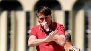 Brazilian President Jair Bolsonaro coughs as he speaks after joining his supporters who were taking part in a motorcade to protest against quarantine and social distancing measures to combat the new coronavirus outbreak in Brasilia on April 19, 2020