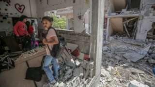 Palestinian girls inspect a destroyed house in Gaza