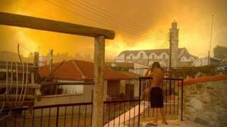 A child in Ora village, near Larnaca, looks as smoke rises from a wildfire. Photo: 3 July 2021