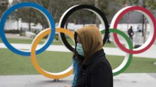 A woman in a face mask walks in front of the Olympic rings in Tokyo