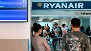 Cancelled Ryanair flights are seen on the announcement board as Ryanair passengers line up at the ticket counter at the terminal of the Skavsta Airport in Nykoeping, Sweden