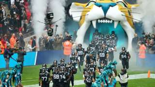 The Jacksonville Jaguars run out from a tunnel of the Jaguar logo at Wembley Stadium