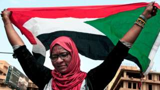 A woman waves a Sudanese national flag during a mass demonstration on 12 September 2019
