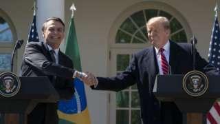 Bolsonaro e Trump apertam as mãos e sorriem em encontro nos EUA