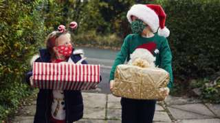 Children with Christmas presents and face coverings