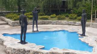 Three figures urinate in a pool shaped like Bosnia and Hercegovina