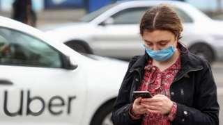 A woman wearing a face mask uses a phone as an Uber passes by in the background.
