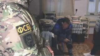 """Кадры видео с совместной операцией ФСБ полиции и Росгаврдии по задержанию пяти подозреваемых членов """"Хизб ут-Тахрир"""" в Бахчисарае, Крым. Задержанные подозреваемые, как утверждается, вербовали новых членов среди мусульман Крыма и распространяли террористическую идеологию."""