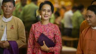 """Myanmar""""s National League for Democracy (NLD) chairperson Aung San Suu Kyi (C) leaving after the new lower house parliamentary session in Naypyidaw"""