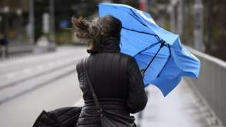 A Swiss woman battles against the wind