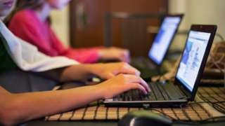 Stock image of children using laptops