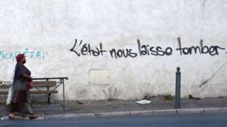 """A woman walks in a street in """"Les marronniers"""" neighbourhood as a handwritting reads 'State lets us down' on the wall, on August 30, 2021"""