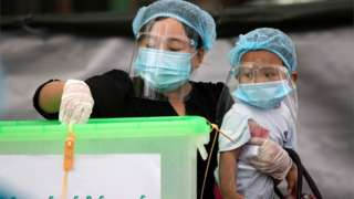 A woman in a mask, hair net and wearing gloves puts her vote in a ballot box while holding her child in Myanmar