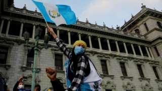 Un mujer con una bandera de Guatemala protesta frente a la sede del Congreso