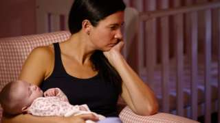 worried looking woman holding baby