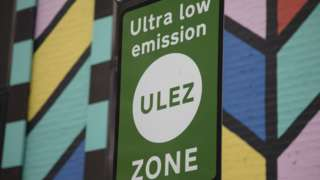 An ultra low emission zone sign in London, against a mural wall's bright colours