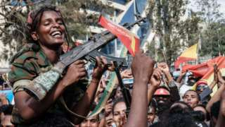 Female soldiers of Tigray Defence Force (TDF) celebrate while they sit on men's shoulders as people celebrate their return on a street in Mekelle