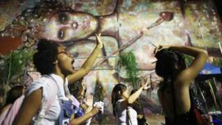 Activists march for pro-choice rights past street art displayed on a wall on September 28, 2017 in Rio de Janeiro, Brazil.
