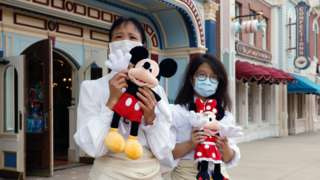 Staff members wearing face mask greet the guests during the reopening day of Disneyland to the public, after a second closure due to the coronavirus disease (COVID-19) outbreak, in Hong Kong, China, September 25, 2020.