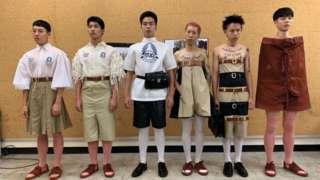 เด็กผู้ชายหกคนในชุดเครื่องแบบนักเรียนที่ต่างไปจากปกติ