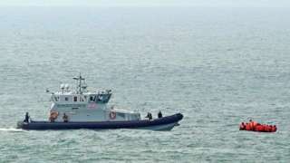 Border Force vessel in the English Channel with a small boat carrying people in life jackets