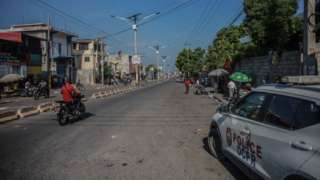 Pipo ride motorcycle past one police car afta call for a general strike wey several professional associations and companies call for to denounce insecurity for Port-au-Prince on October 18, 2021.
