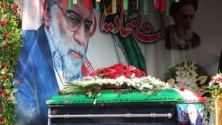 The coffin of Mohsen Fakhrizadeh is displayed in front of a painting of the assassinated nuclear scientist in Tehran, Iran (30 November 2020)