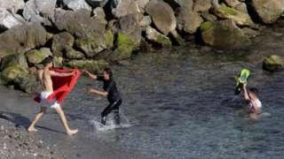 Migrants swimming ashore in Ceuta, 17 May 21