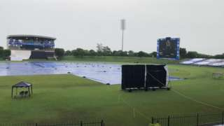 The covers on as rain falls at the MRIC Stadium in Hambantota, Sri Lanka on day two of England's warm-up match