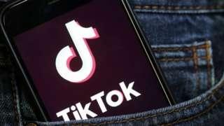 TikTok's logo is displayed on a phone.